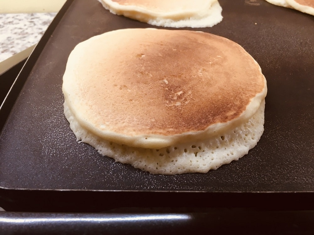 A close look at a cooking pancake that is starting to puff up.
