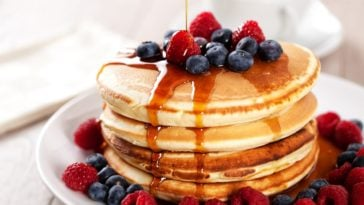 A delicious plate of pancakes with berries and maple syrup.