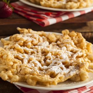 A plate of homemade funnel cakes with white sugar on top.