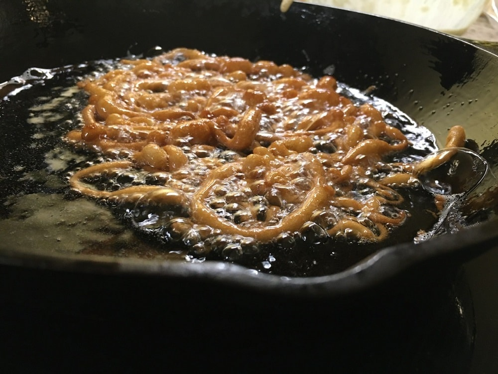 A close up of the funnel cake when it is fully brown in the oil.