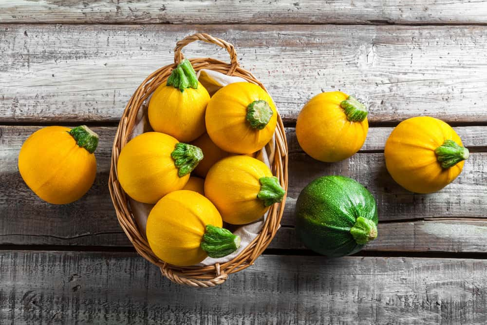 A basket of golden egg zucchinis on a wooden surface.