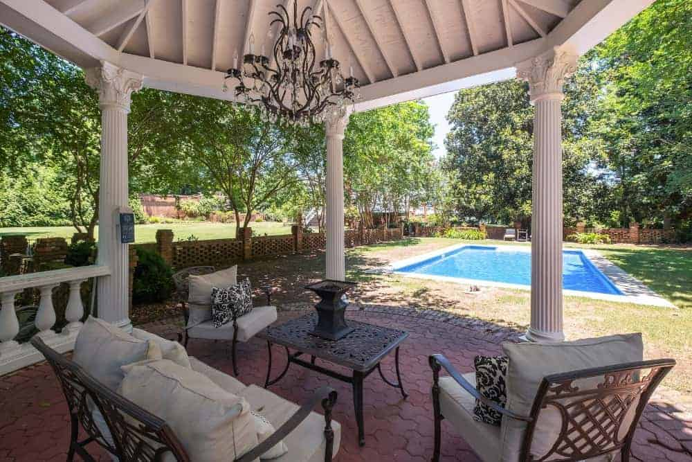 This is the elegant covered patio that has a majestic chendelier hanging over the outdoor sofa set on the terracotta brick flooring. This transitions to a grass lawn before reaching the pool area.