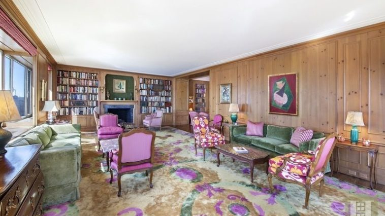 This is the large living room of the apartment with chi c purple elements on its carpeted flooring, throw pillows on the couch and the upholstery of the armchairs. You can also see here the library at the far end. Images courtesy of Toptenrealestatedeals.com.