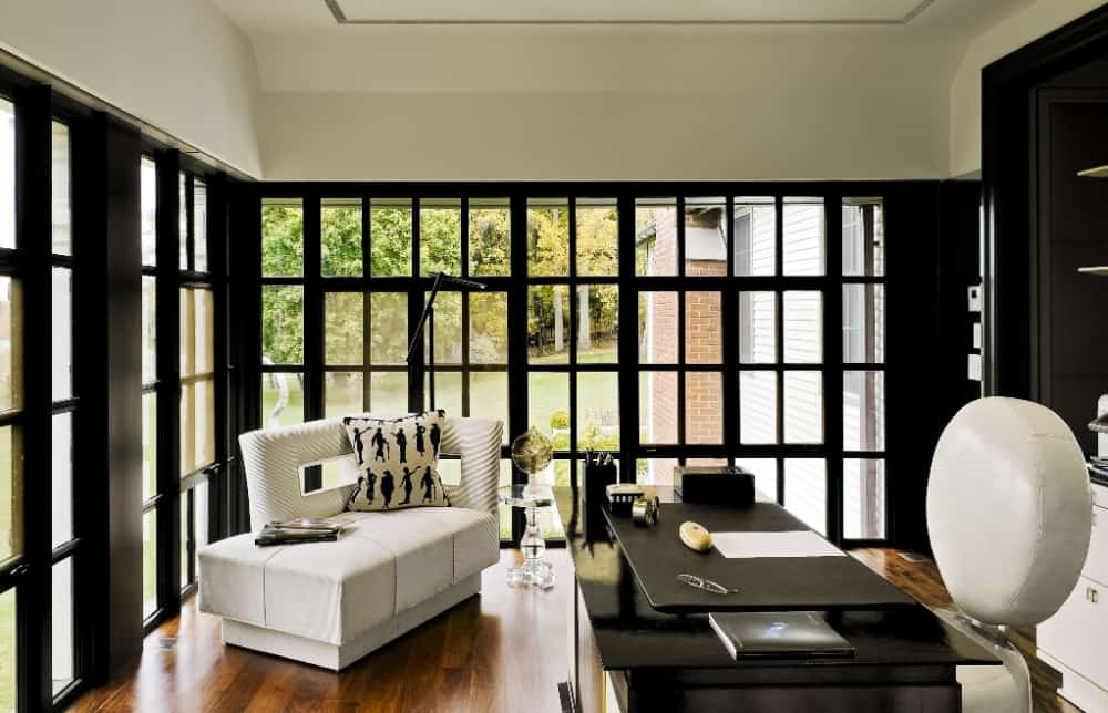 This is a stylish home office with a sleek black desk to match the surrounding window frames that contrast the white ceiling and the modern sofa at the corner.