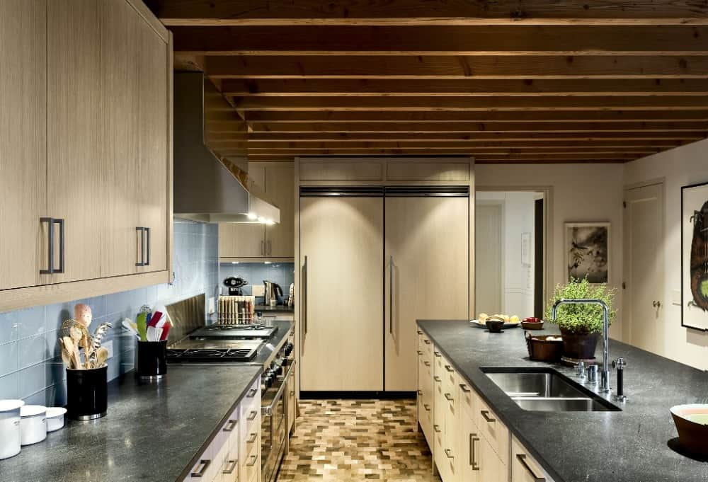 This is a long and narrow kitchen with beige cabinetry complemented by the black countertops illuminated by the warm lights coming from the beamed ceiling.