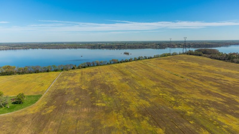This is an aerial view of the property's wide farm property with a large body of water beside it. Images courtesy of Toptenrealestatedeals.com.