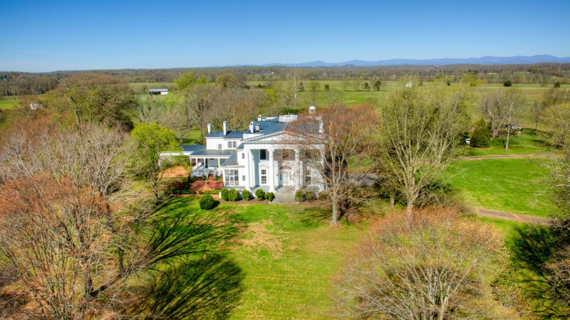 This aerial view of the house showcases the brilliant white exteriors of the house that stand out against the surrounding grass, tall trees and shrubs of the landscape. Images courtesy of Toptenrealestatedeals.com.