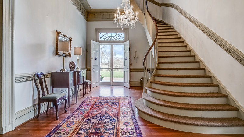 This is a charming foyer with hardwood flooring mostly covered by a patterned area rug topped with a majestic chandelier hanging from the tall ceiling. Images courtesy of Toptenrealestatedeals.com.