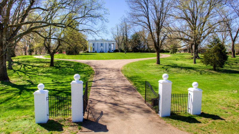 This is the gate entry of the property with thin wrought iron fences supported by white posts. Images courtesy of Toptenrealestatedeals.com.