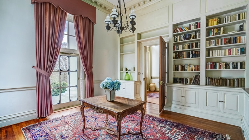 This library has lovely tall beige walls adorned with tall glass windows and built-in wooden shelves that contrast the dark hardwood flooring and its area rug. Images courtesy of Toptenrealestatedeals.com.