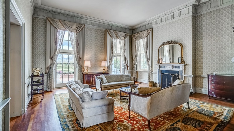 This elegant living room has three beige sofas that stand out against the colorful patterned area rug. These sofas match with the tall beige walls that has tall windows and a fireplace. Images courtesy of Toptenrealestatedeals.com.