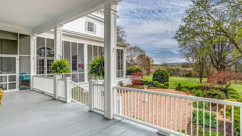 This is the view of the back of the house from the vantage of the back covered patio with lovely white railings that pair with white pillars adorned with potted plants. Images courtesy of Toptenrealestatedeals.com.