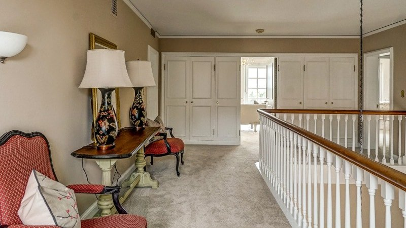 This is the second floor indoor balcony and hallway with a wooden console table on the side flanked by armchairs. Images courtesy of Toptenrealestatedeals.com.