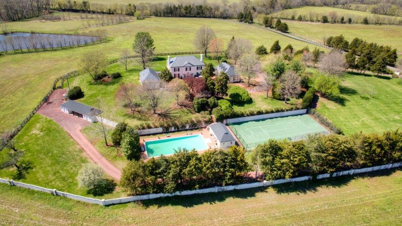 This view shows the two outdoor areas of the property like the pool and the tennis court beside it. Images courtesy of Toptenrealestatedeals.com.