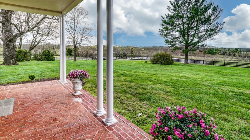 This is the view of the lush backyard grass lawn from the vantage of the covered patio adorned with potted flowering plants. Images courtesy of Toptenrealestatedeals.com.