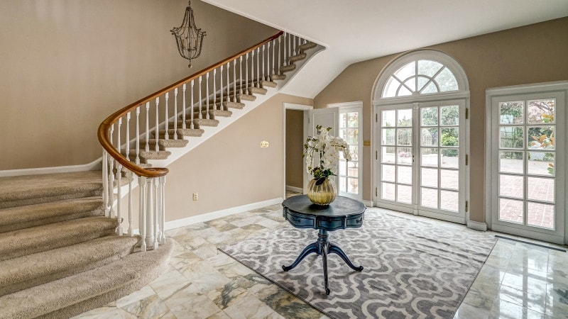 The charming foyer has a gray patterned area rug over the beige marble floor with a small round table in the middle bearing a flower vase. Images courtesy of Toptenrealestatedeals.com.