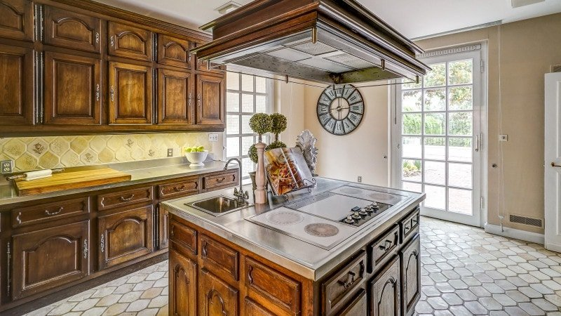 The kitchen has elegant dark wooden cabinetry that matches perfectly with the kitchen island in the middle where the cooking area is topped with a large vent hood. Images courtesy of Toptenrealestatedeals.com.