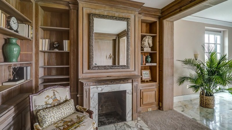 This is a close look at the lovely library with a fireplace housed in a large wooden structure that has a large mirror and built-in shelves on each side of the fireplace. Images courtesy of Toptenrealestatedeals.com.