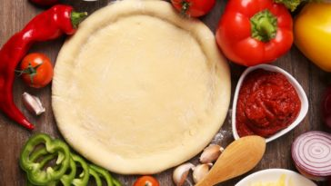 A homemade pizza dough with pizza ingredients around it.