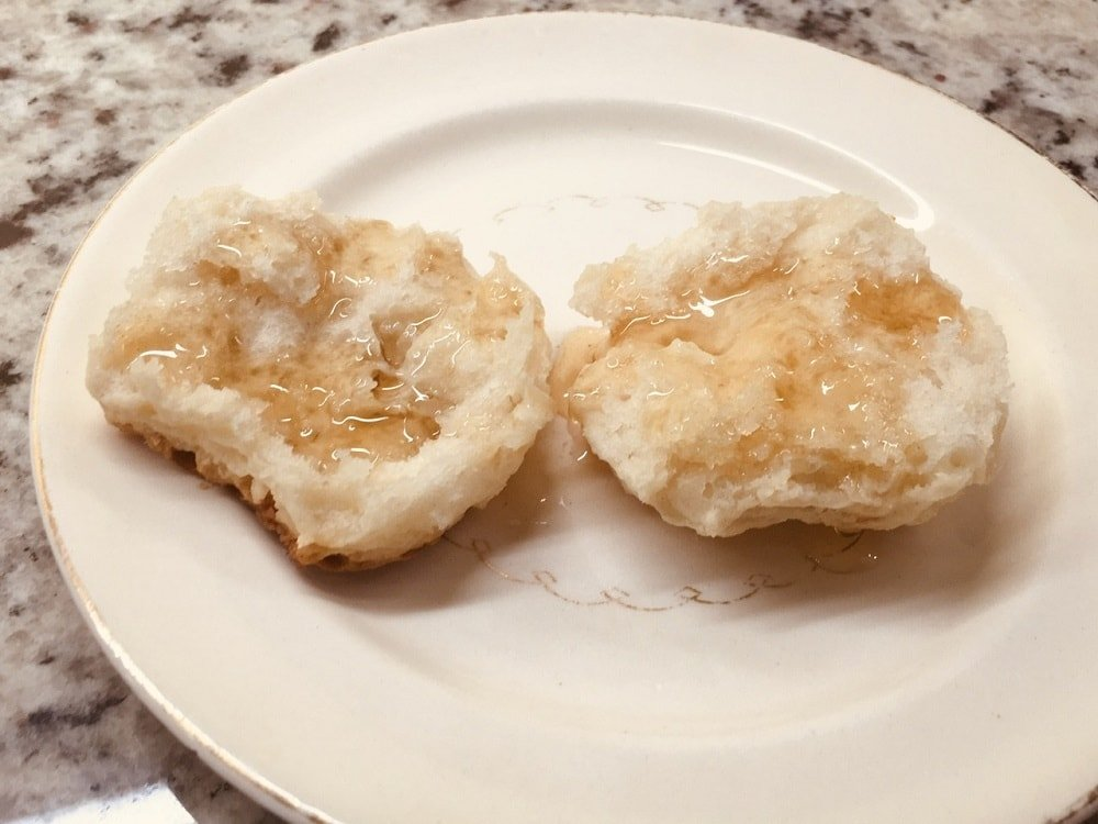 A halved homemade biscuit on a plate with maple syrup.