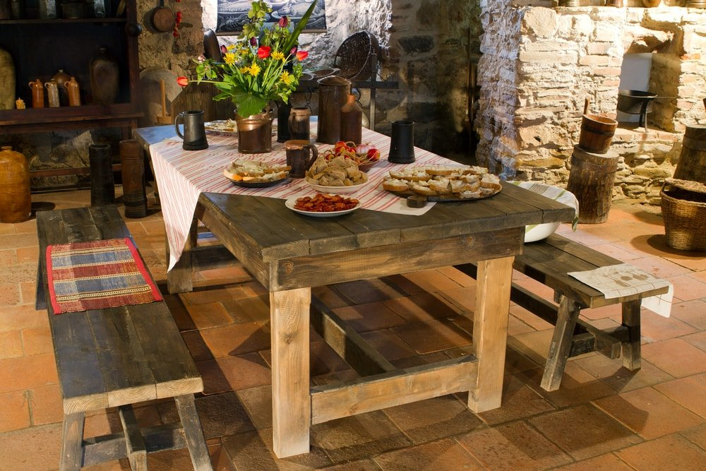 A lovely rustic dining table paired with matching wooden benches on terracotta flooring tiles.