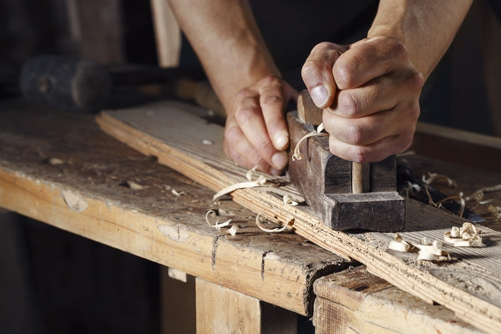 A close up of a carpenter planing the plank with a wood plane.