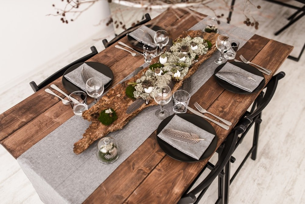 A charming and rustic wooden dining table paired with black chairs.