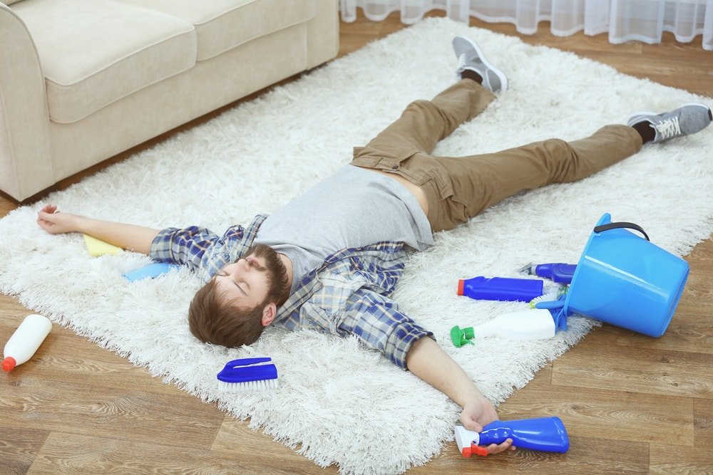 A man lying the carpet tired from cleaning.
