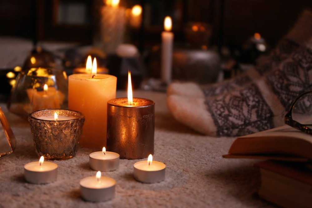 A bunch of lit candles on a carpeted flooring.