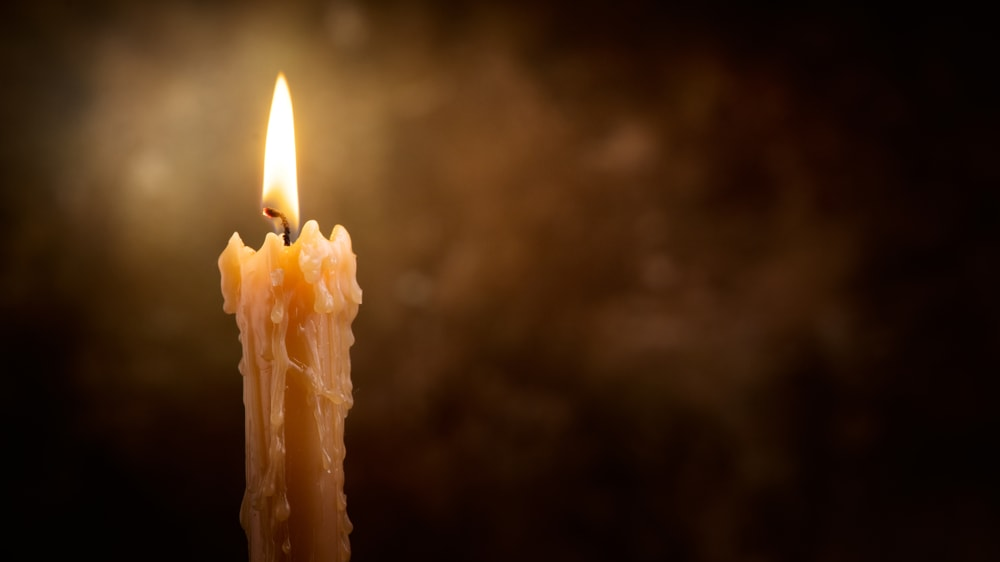 A lit yellow candle against a dark background.