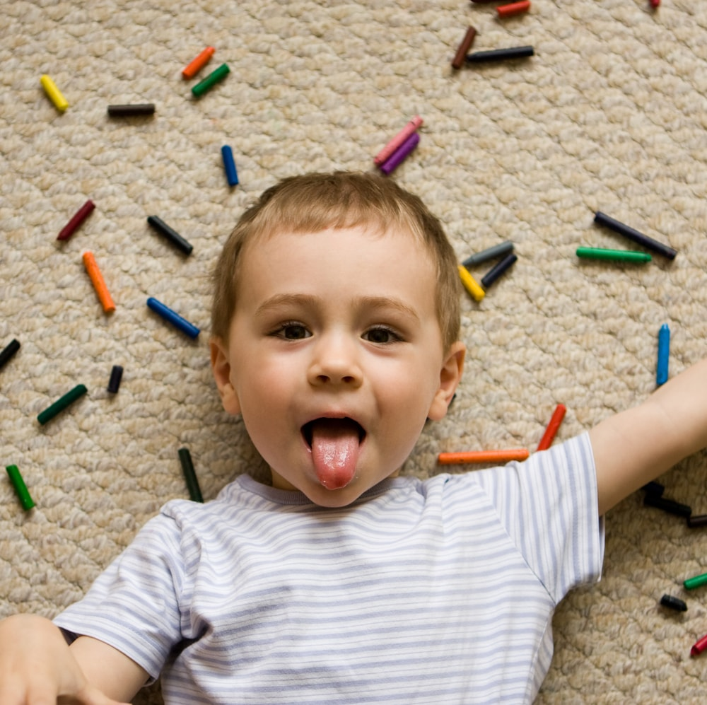 A kid playing with colorful crayons on the beige carpet.
