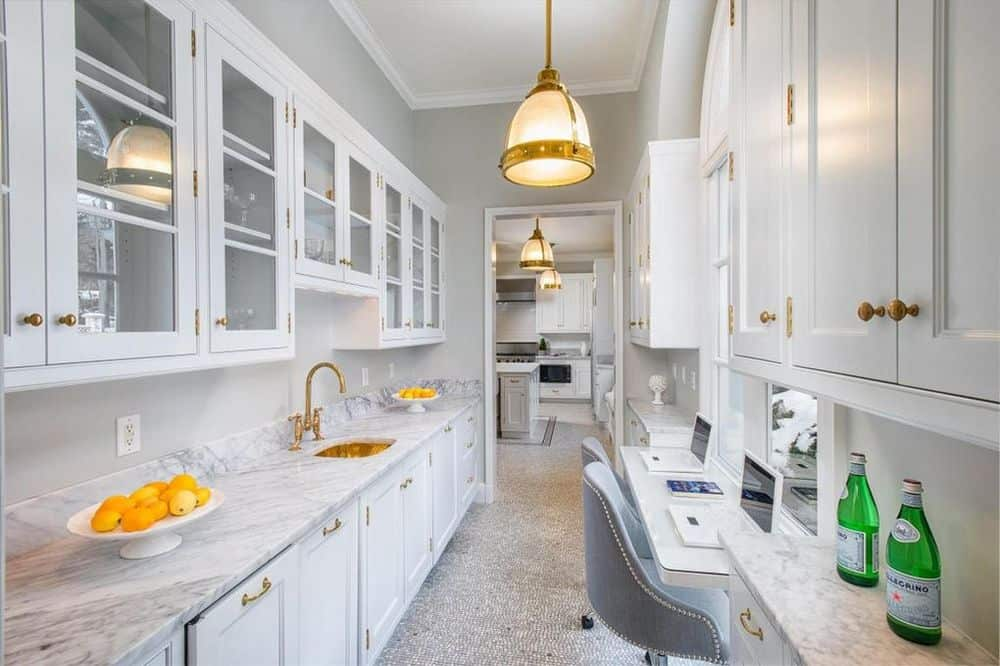 This is the long and narrow kitchen with white cabinetry matched by the white marble countertops. There is also a built-in desk paired with gray cushioned chairs.
