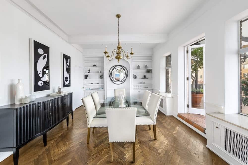 The white formal dining room has gorgeous herring bone hardwood flooring and a majestic chandelier over the glass-top dining table. On the side is a black cabinet topped with black artworks to stand out against the white wall.