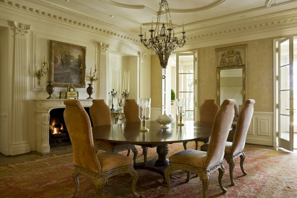 This is the formal dining room that has a large elliptical dark wooden dining table surrounded by cushioned chairs and warmed by the fireplace that is topped with a classic painting. Images courtesy of Toptenrealestatedeals.com.