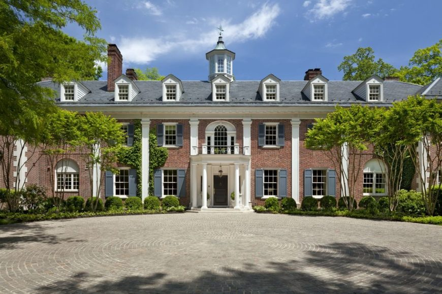This is the front view of this majestic traditional Georgian-style mansion with tall pillars, a row of dormer windows and a large courtyard and driveway lined with shrubs and tall trees. Images courtesy of Toptenrealestatedeals.com.