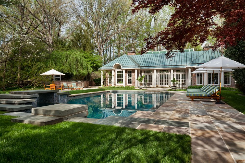 This is the gorgeous pool surrounded by concrete walkways, lush landscaping and a large pool house on the far side with a beautiful blue roof. Images courtesy of Toptenrealestatedeals.com.