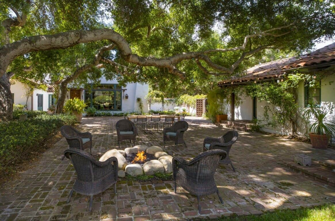 This is the charming backyard patio with a set of outdoor armchairs surrounding the rustic firepit in the middle of the brick flooring under the shade of a big tree.