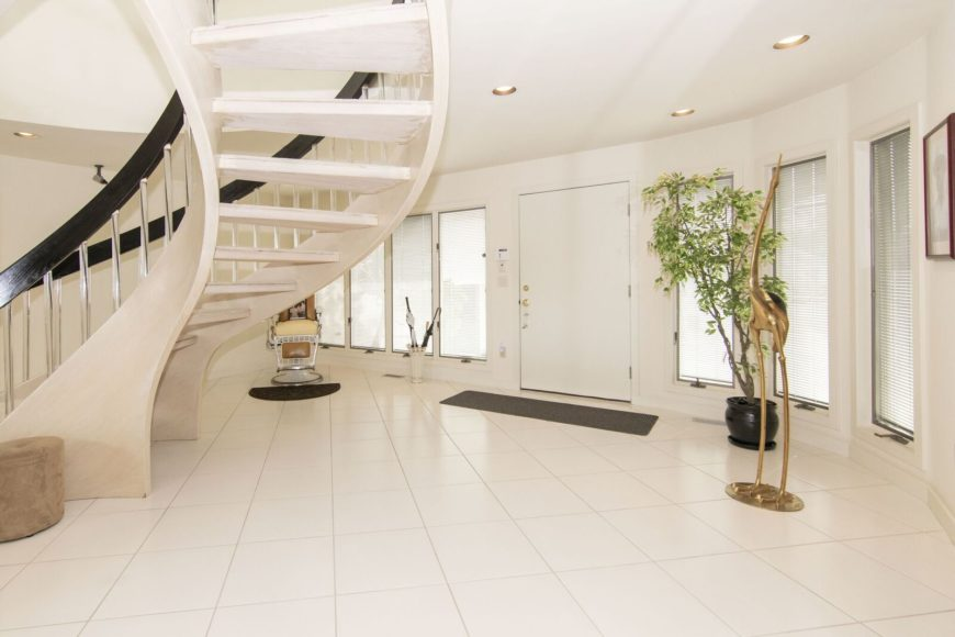This is a bright and spacious foyer with white walls, white flooring tiles, white ceiling and a white spiral staircase. These are contrasted by the black banisters of the staircase, welcome mat and the black pot of the plant in the corner.