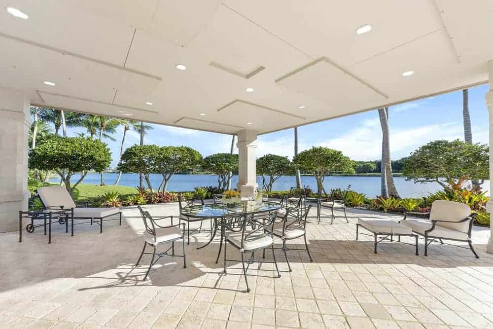 This is the gorgeous covered patio with a tall patterned white ceiling with recessed lights. This is complemented by outdoor tiles and open walls featuring the beautiful scenery of the landscaping as background for the outdoor dining and sitting areas.