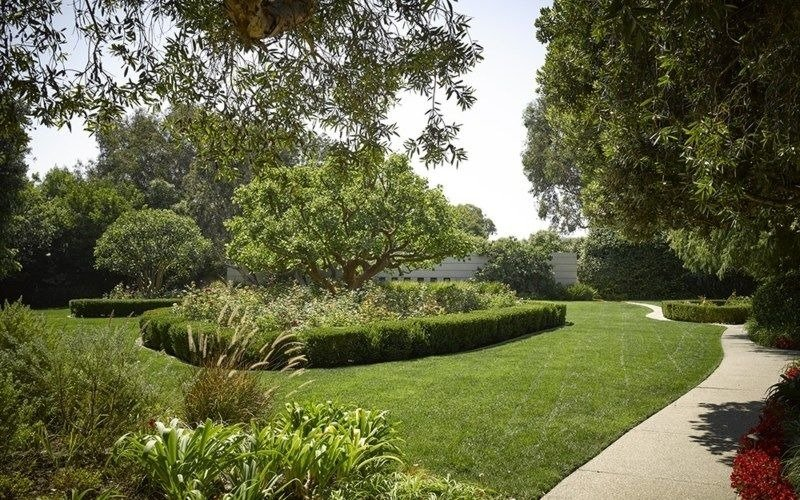 The home also has a lawn area in its garden, featuring a side walkway. Images courtesy of Toptenrealestatedeals.com.