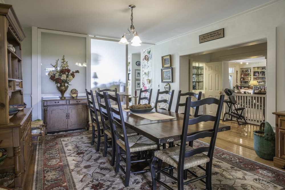 This lovely dining room has a large wooden rectangular dining table surrounded by the matching dark wooden chairs with cushioned seats. These are then contrasted by the bright beige walls and ceiling that hangs a simple lighting over the table. Images courtesy of Toptenrealestatedeals.com.
