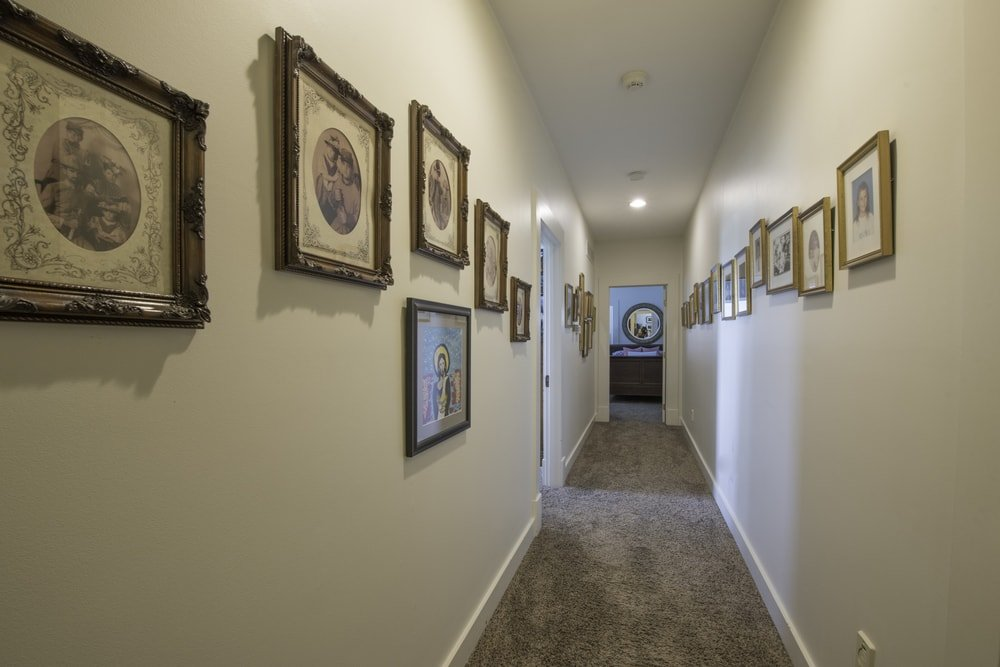 This is the homey hallway with beige walls adorned by multiple framed artworks that stand out with their dark wooden frames. Images courtesy of Toptenrealestatedeals.com.