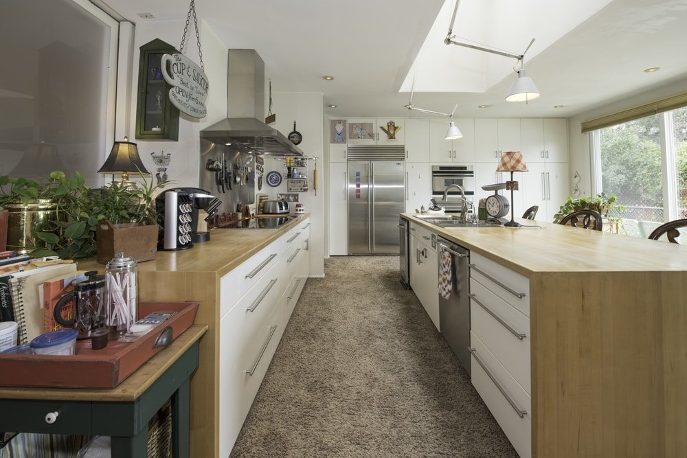 This is the galley kitchen with bright white cabinetry that matches the walls and ceiling brightened by the skylight.
