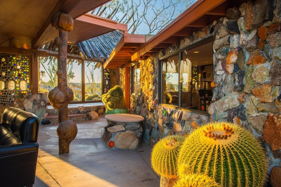 This is the covered open area of the house with beautiful mosaic stone walls, unique wooden pillars and stone flooring that is adorned with cacti. Images courtesy of Toptenrealestatedeals.com.