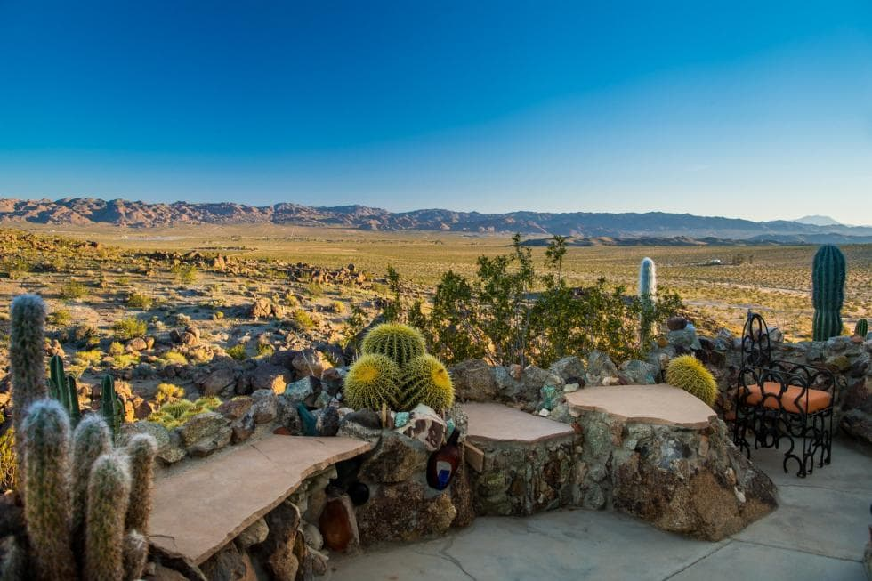 This overlooking area has a scenic view of the Joshua Tree desert in the distance. This area is fitted with rustic and charming benches adorned with cacti and succulents. Images courtesy of Toptenrealestatedeals.com.