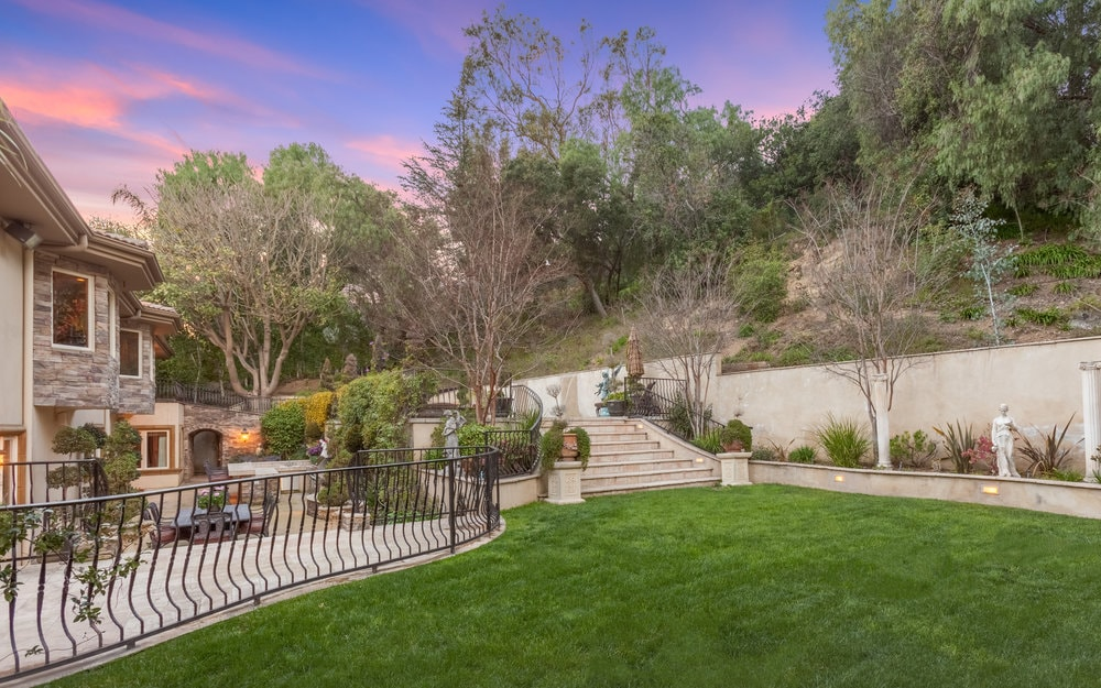 There is a lush grass lawn at the back of the house adorned with shrubs, potted plants and concrete steps. There are tall trees in the background that provide privacy and shade. Images courtesy of Toptenrealestatedeals.com.