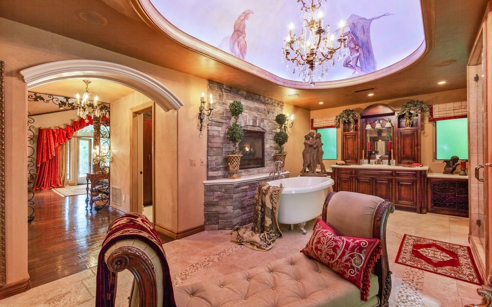 The spacious primary bathroom has a bright cove ceiling that hangs a chandelier in the middle. There is a freestanding bathtub placed by the stone wall that houses a fireplace adorned with potted plants. Images courtesy of Toptenrealestatedeals.com.