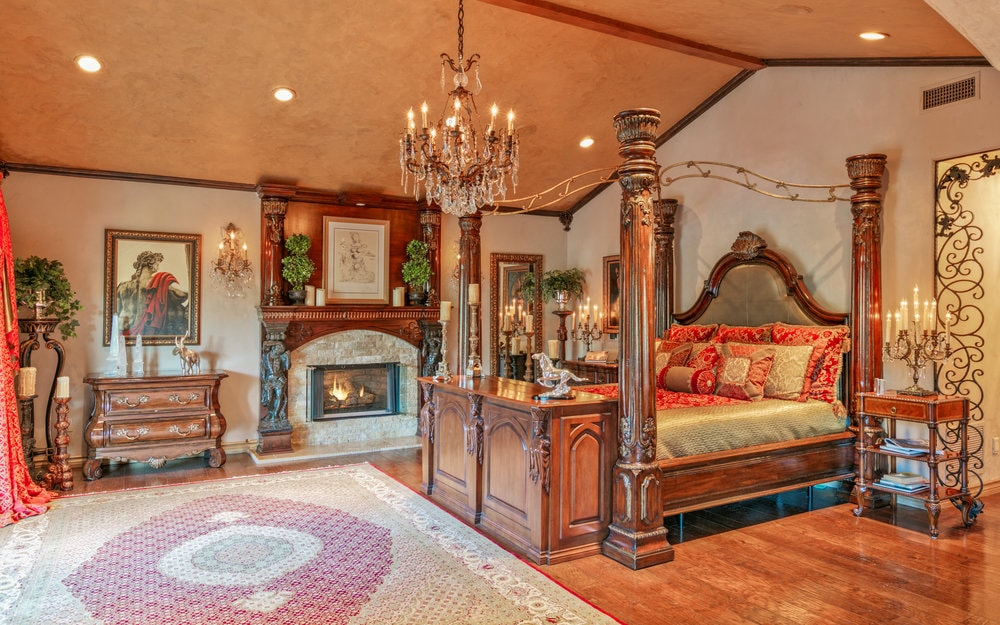 The primary bedroom has a large dark wood four-poster bed complemented by a crystal chandelier and a fireplace on the side. Images courtesy of Toptenrealestatedeals.com.