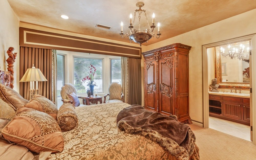 This other bedroom has a large bed topped with a simple chandelier. On the side is a lovely sitting area by the glass walls that brighten the wooden cabinet. Images courtesy of Toptenrealestatedeals.com.