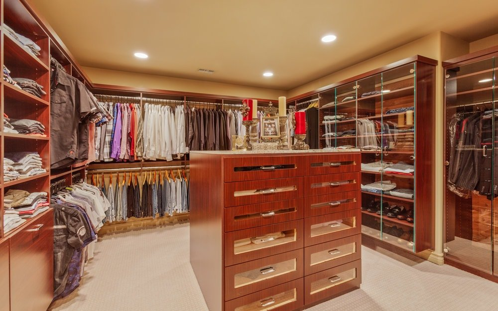 The spacious walk-in closet as a dark wooden island that is surrounded by the built-in racks and shelves of the walls. It has a beige ceiling with recessed lights. Images courtesy of Toptenrealestatedeals.com.